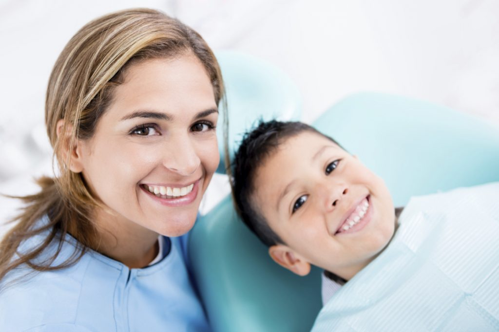 Dentist with a young patient looking very happy